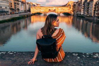 vrouw zittend op een brug bij een rivier