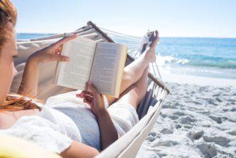 vrouw leest boek in hangmat op het strand